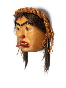 A carved wooden mask of a female face with black eyebrows. The mask has long dark hair and a hairband made of woven cedar bark. Its nose and mouth are painted red, and a red tongue is sticking out of its mouth.