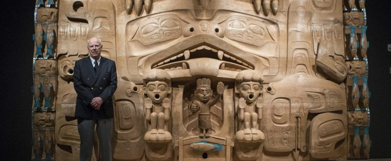 """A man wearing a double-breasted black suit jacket and grey pants stands with his hands together towards the camera. Behind him is a wall-sized carving of light-coloured wood, """"The Dance Screen"""" by James Hart. Symmetrical animal figures including a bear, thunderbird, orca, and many salmon are carved in deep relief. The salmon carvings have shiny abalone inlays."""