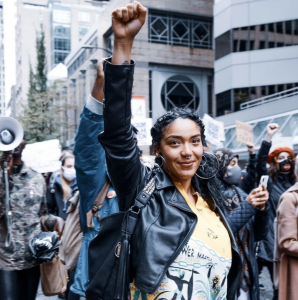 A smiling Xhalida September holds up her fist in the midst of a march. People behind her carry signs and wear masks.