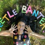 A smiling person lies on the grass. Their hands are open, facing the camera. Above them cut out letters spell Beetle Banter.