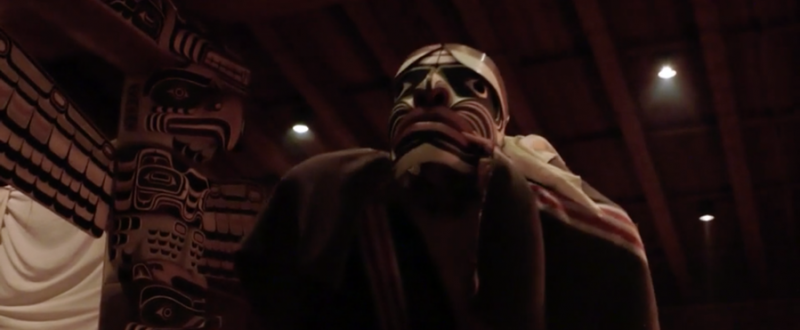 A person wearing a Kwakwaka'wakw earthquake mask dances. Behind is a totem pole on the left, and an audience on the right.
