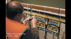William White sits, weaving a blue, yellow and white Chilkat robe at MOA. Text in the bottom left corner reads William White weaving at MOA, 2002.