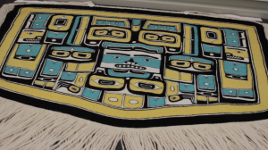 A blue, white and yellow woven Chilkat robe, with Northwest Coast style motifs. A white fringe hangs down.