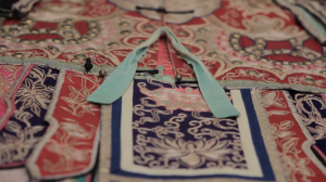 Close up of the transformation robe, showing turquoise ties and rich colourful embroidery.
