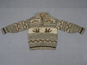 A grey, brown and beige knit Cowichan sweater laying flat. The central motif shows two swallows flying toward each other.