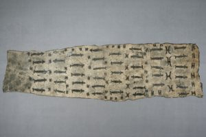 A long narrow barkcloth with repeating designs in rows: a human-like figure with a long body and a sideways 'H' shape.