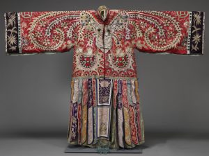 A colourful transformation robe on display, with wide sleeves. A large embroidered bat is in the centre of the robe.