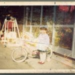 A rescued damaged photo of a small child standing next to a bike. A small swing is in the background.